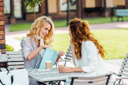 fashionable young women checking buys while sitting in cafe after shopping Stock Photo