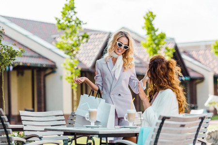 stylish young women spending time together in cafe after shopping Stock Photo