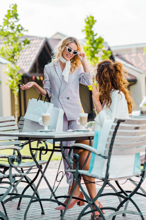 fashionable young women spending time together in cafe after shopping Stock Photo