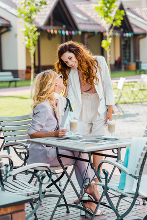 beautiful young women spending time together in cafe after shopping