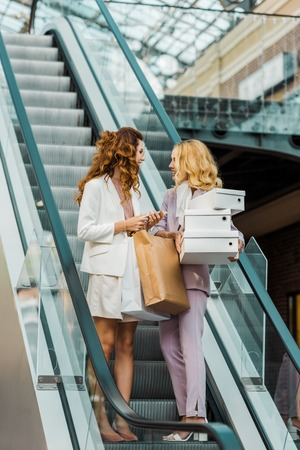 stylish young women with shopping bags and boxes on escalator at mall Stock Photo