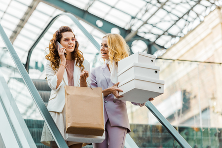 beautiful young women with shopping bags and boxes on escalator at mall Stock Photo