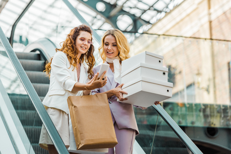 beautiful young women with shopping bags and boxes looking at smartphone on escalator at mall