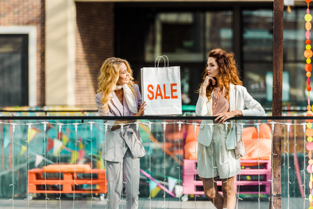 attractive young women spending time together in mall with shopping bag with sale sign