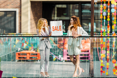 beautiful young women spending time together in mall with shopping bag with sale sign