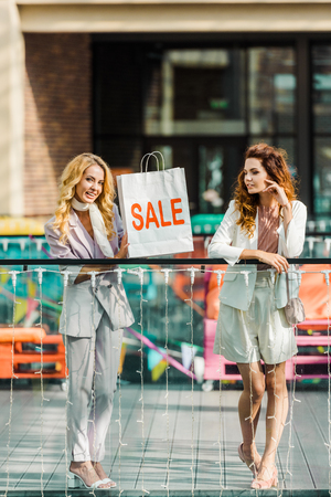 fashionable young women spending time together in mall with shopping bag with sale sign