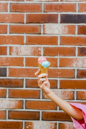 cropped shot of woman holding delicious ice cream in waffle cone in front of brick wall Imagens