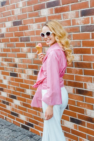 smiling young woman in pink holding ice cream and looking at camera in front of brick wall Imagens
