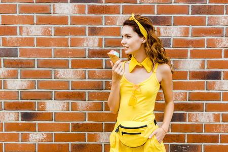 beautiful smiling woman in yellow clothes with ice cream posing in front of brick wall