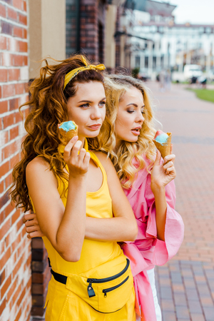 beautiful young women in colorful clothes eating delicious ice cream on street Imagens