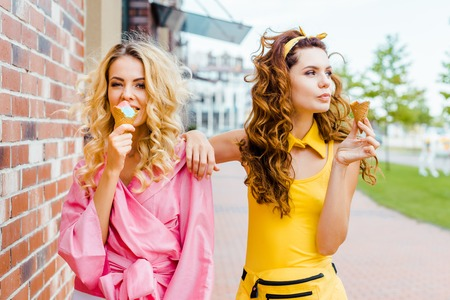 fashionable young women in colorful clothes eating ice cream on street Imagens