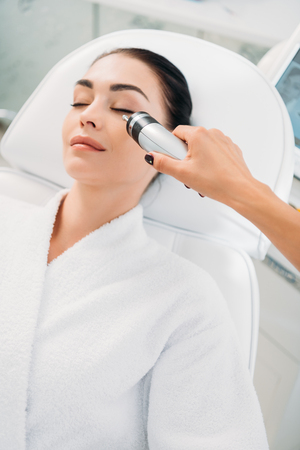 attractive woman getting facial microcurrent therapy in spa salon