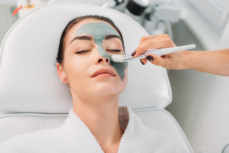 partial view of cosmetologist applying clay mask on female face in spa salon 免版税图像