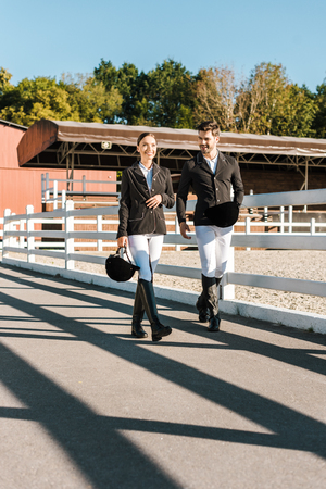 male and female equestrians in professional apparel walking near fence at ranch Stock Photo