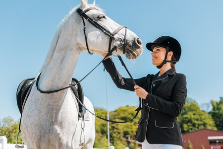 attractive female equestrian palming horse at horse club Stock Photo