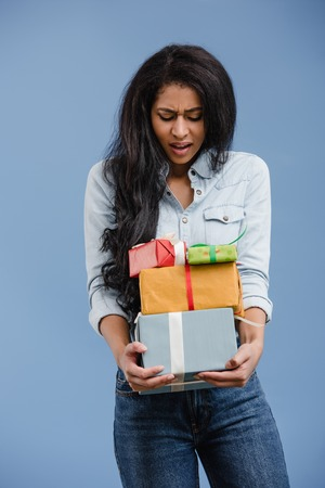 dissatisfied african american girl looking at gift boxes isolated on blue