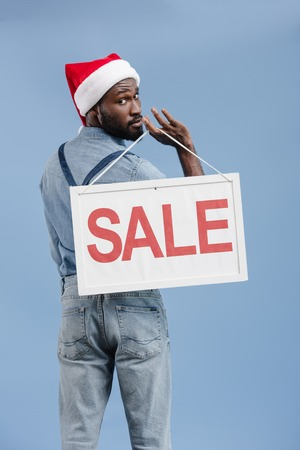 back view of handsome african american man in santa hat holding sale sign isolated on blue Stock Photo