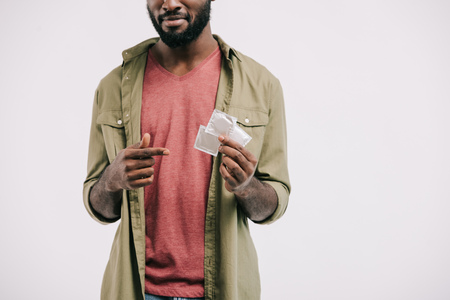 cropped image of african american man pointing on condoms isolated on white