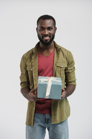 handsome smiling african american man holding present box isolated on white Stock Photo