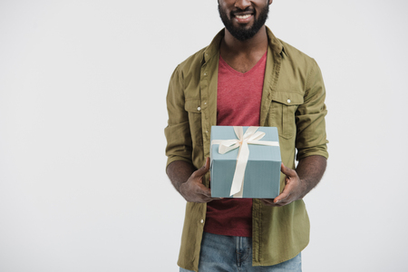 cropped image of smiling african american man holding present box isolated on white Stock Photo