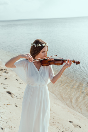 beautiful woman in elegant white dress and floral wreath playing violin on seashore Imagens