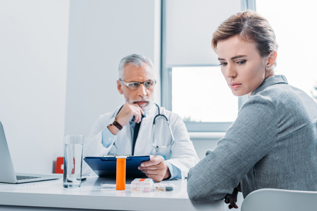 sad female patient looking away while mature male doctor sitting near at table in office Stock Photo