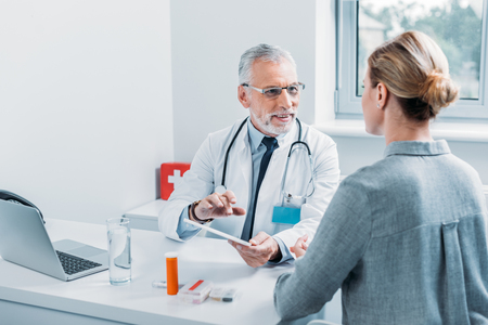 happy mature male doctor using digital tablet and talking to female patient at table in office