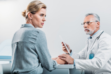 serious male doctor with digital tablet cheering up and holdings hands of upset female patient at table in office