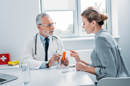 middle aged male doctor pointing at pills to female patient at table in office