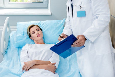 partial view of male doctor with stethoscope over neck pointing at clipboard to female patient in hospital room Banco de Imagens