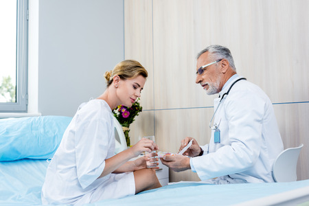 adult female patient with glass of water taking pills from mature male doctor in hospital room