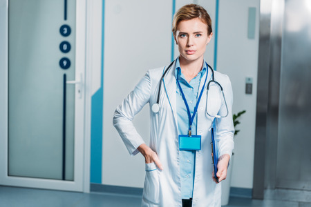 portrait of female doctor with stethoscope over neck holding clipboard in hospital