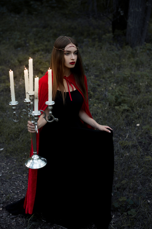 mystic girl in red cloak holding candelabrum with flaming candles walking in forest