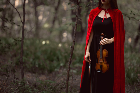 cropped view of elegant woman in red cloak holding violin in dark woods Stock Photo