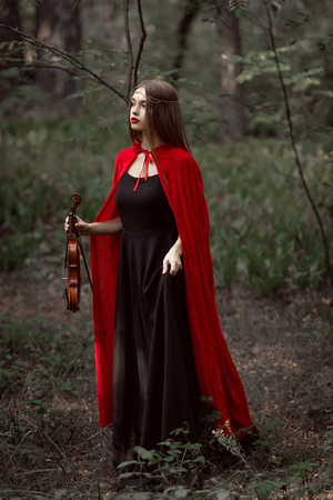 attractive mystic woman in red cloak holding violin in dark forest Stock Photo