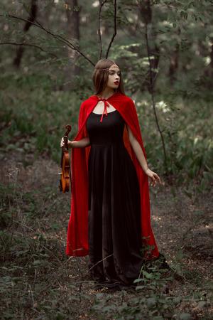 elegant mystic girl in black dress and red cloak holding violin in dark woods Stock Photo