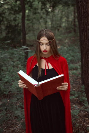 beautiful mystic girl in red cloak and wreath reading magic book in woods 免版税图像