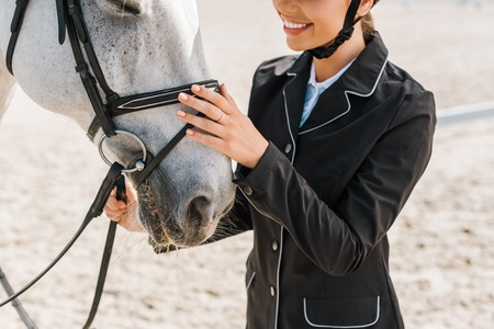 cropped image of smiling female equestrian palming horse at horse club Stock Photo