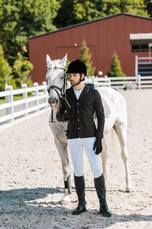 handsome male equestrian standing near horse and looking away at horse club