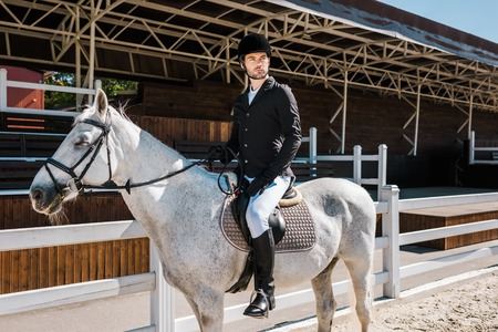 handsome male equestrian riding white horse at horse club Stock Photo
