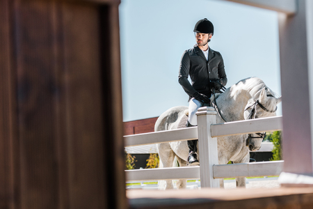 view through fence on handsome male equestrian in professional apparel sitting on horse at ranch