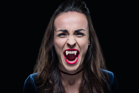 gothic woman showing vampire teeth isolated on black Imagens
