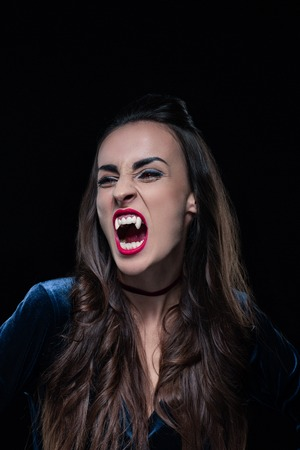 beautiful woman showing vampire teeth isolated on black