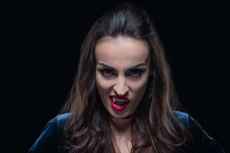horror woman showing vampire fangs isolated on black