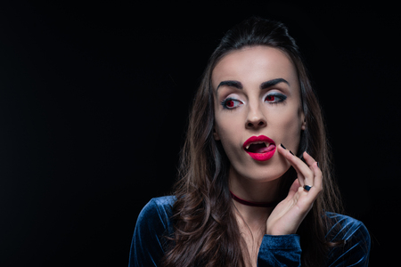 vampire woman touching her tongue isolated on black Stock Photo