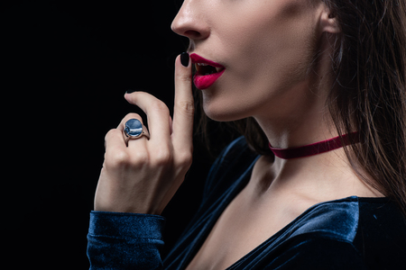 cropped view of vampire showing silence symbol isolated on black Stock Photo