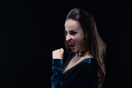dreadful woman showing vampire teeth isolated on black