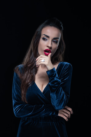 beautiful vampire touching her lips isolated on black Stock Photo