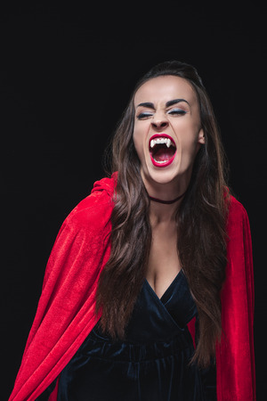 mystic vampire woman in red cloak showing her teeth isolated on black Фото со стока