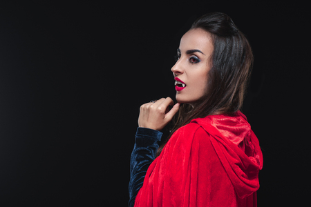 beautiful vampire woman in red cloak isolated on black